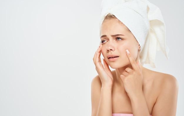 Femme avec une serviette blanche sur la tête touche son visage avec ses mains sur un fond clair