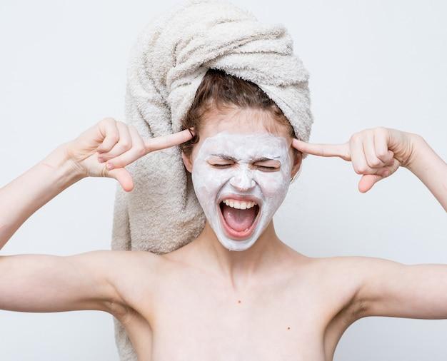 Femme avec une serviette épaules nues sur la tête visage masque soins de la peau gros plan.