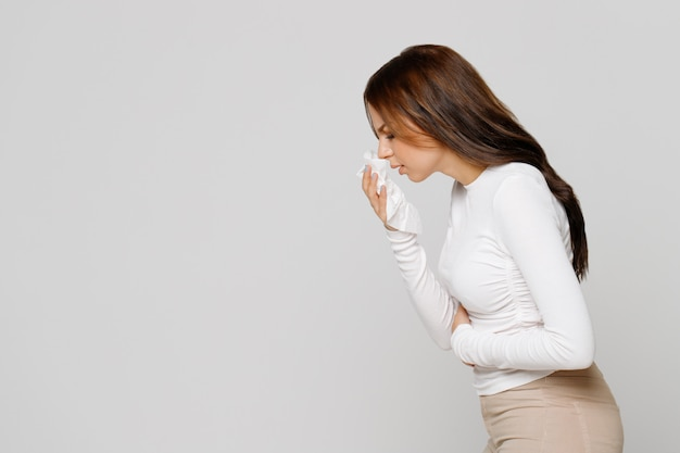 Femme avec une serviette en papier éternue, éprouve des symptômes d'allergie