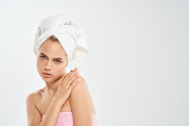 Femme avec une serviette sur sa tête coton peau propre fond clair dermatologie