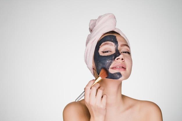 Une femme avec une serviette sur la tête applique un masque nettoyant sur son visage