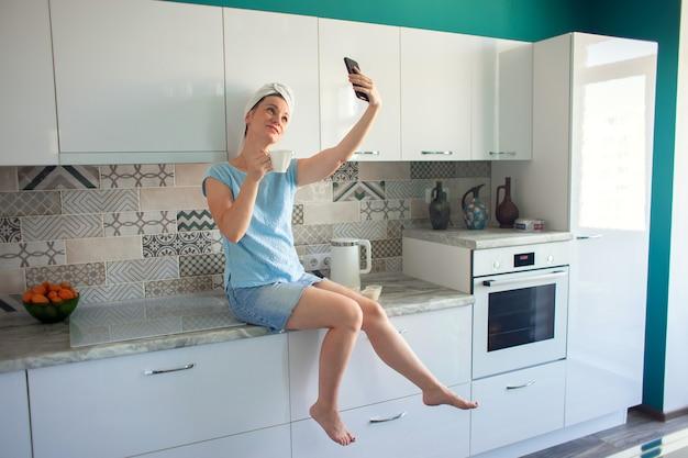 Une femme avec une serviette sur la tête après une douche est assise dans la cuisine avec une tasse de café et se photographie sur un smartphone