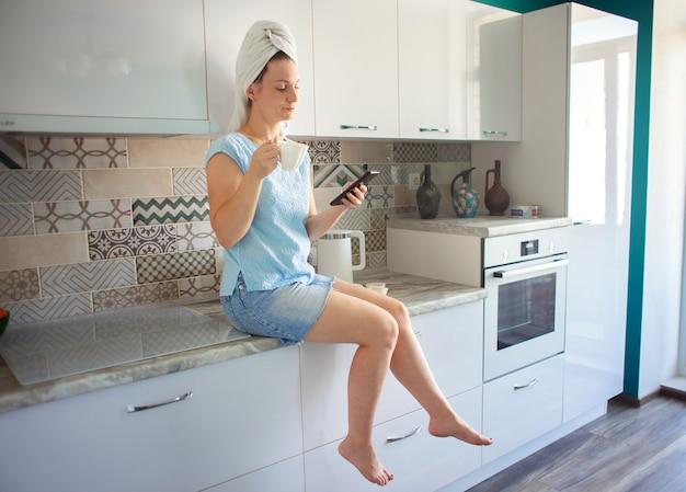 Femme avec une serviette sur la tête dans sa cuisine en train de prendre le petit déjeuner et en regardant le téléphone
