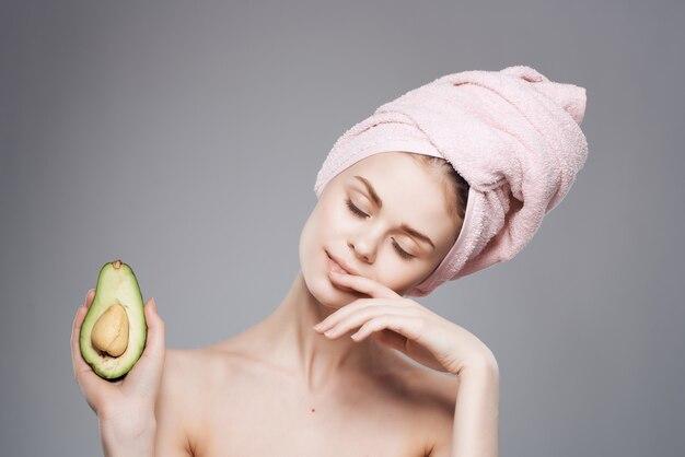 Femme avec une serviette sur la tête épaules nues avocat fruits vitamines santé