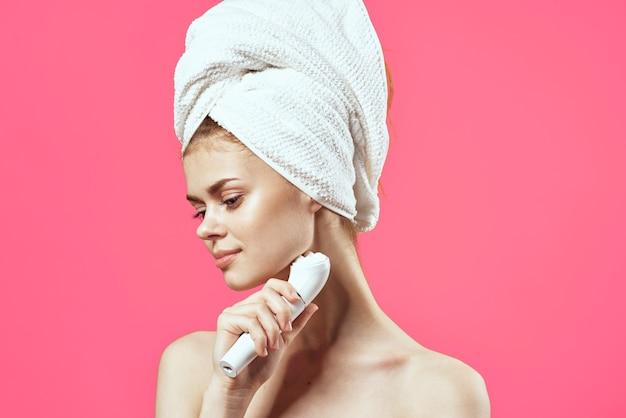 Femme avec une serviette sur la tête épaules nues masser les cosmétiques de médecine. photo de haute qualité