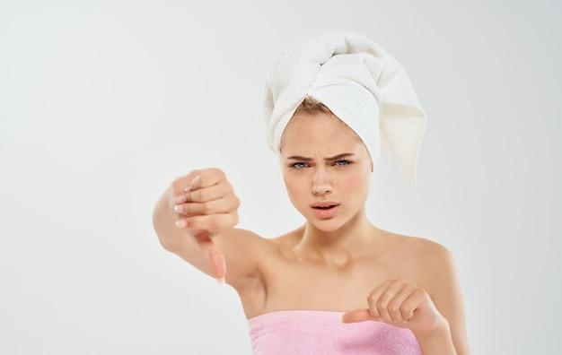 Femme avec une serviette sur la tête, épaules nues, problèmes de cheveux mouillés auxquels nous sommes confrontés avec la peau.