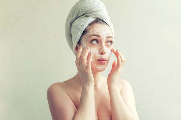 Femme en serviette sur la tête avec masque nourrissant blanc ou crème sur le visage, fond blanc isolé