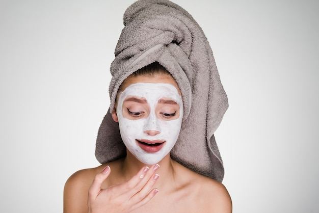 Une femme avec une serviette sur la tête a mis un masque sur son visage