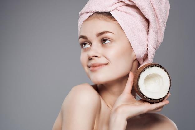 Femme avec une serviette sur la tête de noix de coco soins de la peau fond isolé
