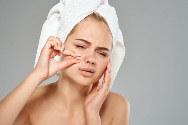 Une femme avec une serviette sur la tête serre des boutons sur son front des problèmes de peau