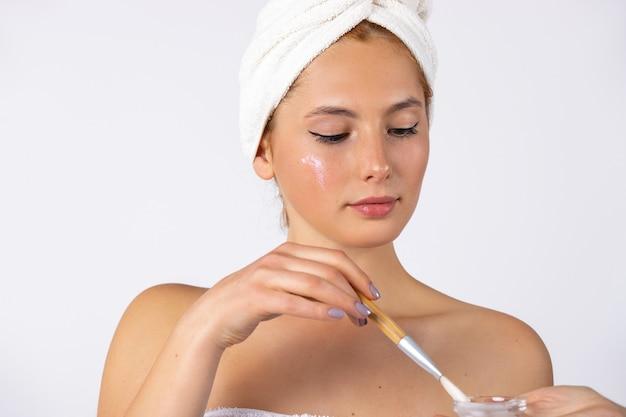 Une femme avec une serviette sur la tête tient une brosse cosmétique près d'un bol avec masque facial photo sur mur blanc