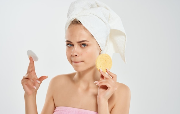 Femme avec une serviette sur la tête tient une éponge dans son modèle de dermatologie cosmétologie main.
