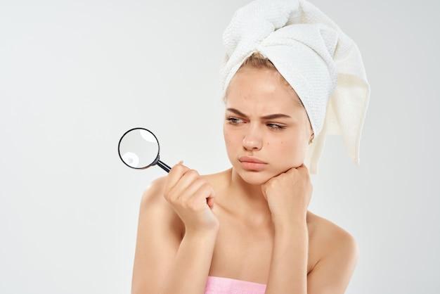 Une femme avec une serviette sur la tête tient une loupe près de l'acné du visage. photo de haute qualité