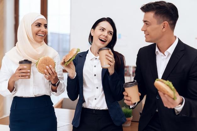 Une femme avec ses collègues en train de manger un hamburger