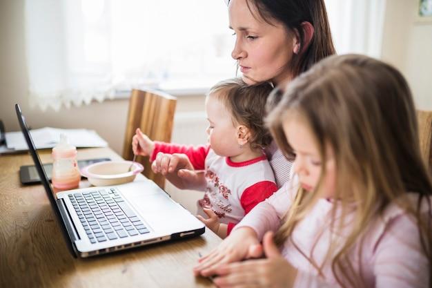 Femme avec ses deux filles mignonnes en regardant un ordinateur portable