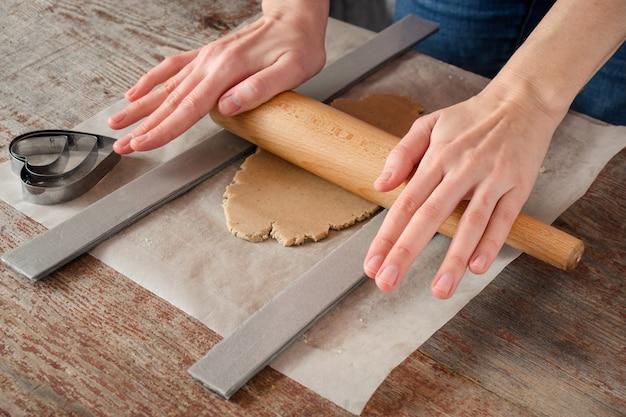 Femme avec ses mains roule de la pâte pour un biscuit avec un rouleau à pâtisserie