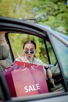 Femme avec ses sacs à provisions dans la voiture - concept de shopping.