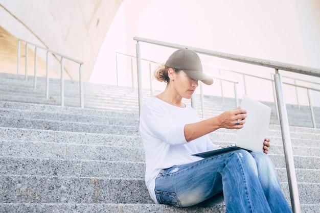 Femme seule assise dans les escaliers avec casquette regardant et travaillant avec son ordinateur portable ou son ordinateur en toute sérénité dans la ville - concept urbain et femme d'affaires en silence