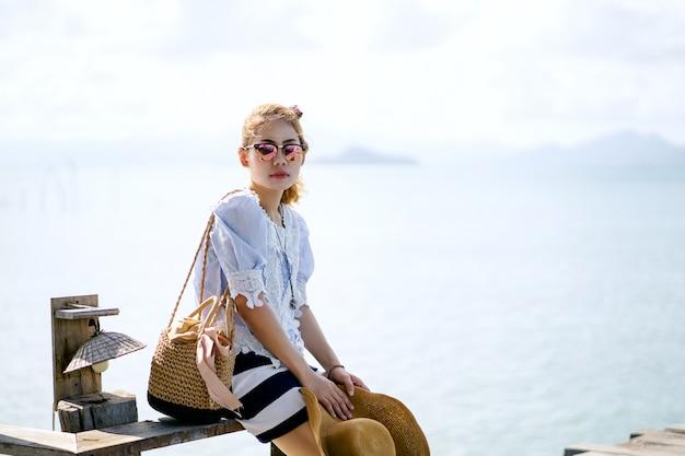 Une femme seule assise sur le pont de bois - koh mark, thaïlande
