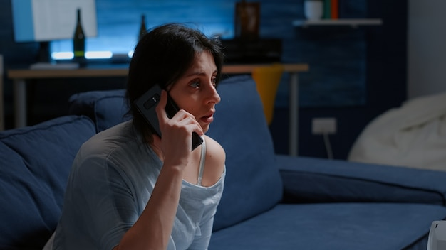 Femme seule choquée recevant des nouvelles tragiques laissant tomber un smartphone