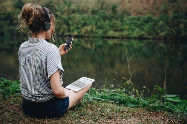 Femme seule dans la nature, écouter de la musique avec des écouteurs, une tablette numérique et un smartphone