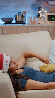 Femme seule mangeant des chips et changeant de chaîne à la télévision