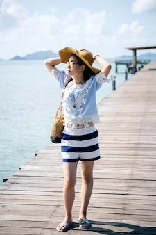 Une femme seule se détendre sur le pont de bois - koh mark, thaïlande