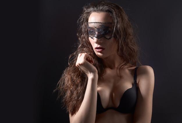 Femme sexuelle posant sur fond sombre avec un masque de dentelle sur les yeux fermés