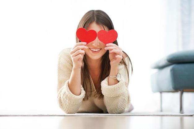 Femme sexy adulte se détendre à la maison tenant des coeurs, concept de la saint-valentin