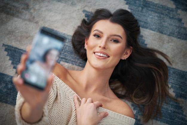 Femme sexy adulte se détendre à la maison et utiliser un smartphone