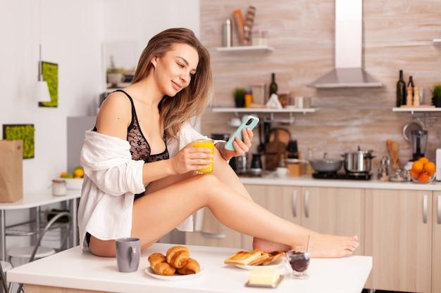 Femme sexy assise sur la table de la cuisine à l'aide d'un smartphone portant des sous-vêtements séduisants. femme séduisante avec des tatouages utilisant un smartphone portant de la lingerie temporaire le matin.