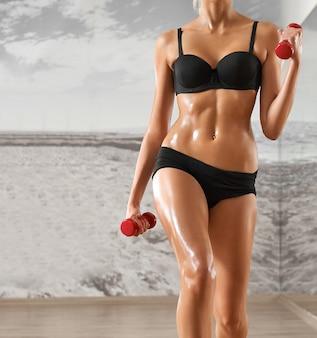Femme sexy, athlétique, blonde dans la salle de gym, dans le contexte