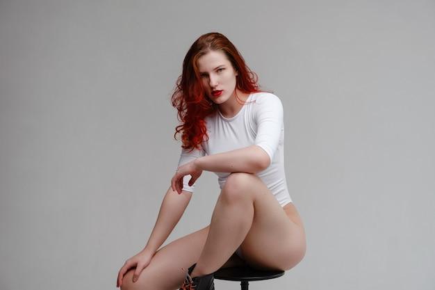 Femme sexy aux longs cheveux roux qui pose en lingerie blanche sur fond de studio blanc. bien-être, épilation, concept de soins du corps. yoga et gym, vraie beauté et corps positif