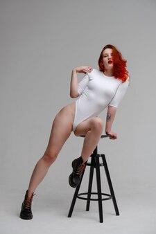 Femme Sexy Aux Longs Cheveux Roux Qui Pose En Lingerie Blanche Sur Fond De Studio Blanc. Bien-être, épilation, Concept De Soins Du Corps. Yoga Et Gym, Vraie Beauté Et Corps Positif Photo Premium