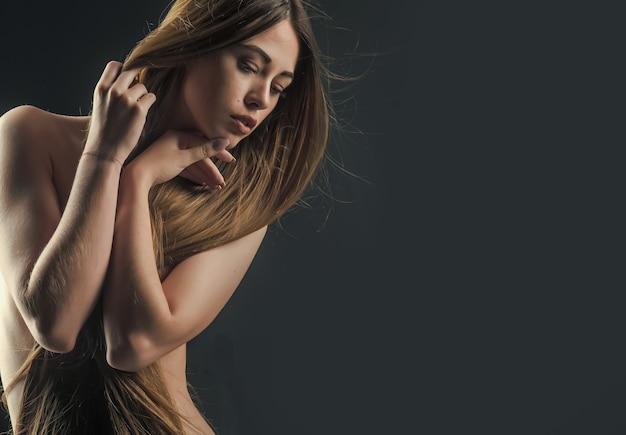 Femme sexy aux longs cheveux sains et corps nu sur fond noir, salon de beauté.