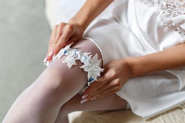 Femme sexy en bas blancs porte une jarretière sur la jambe dans la chambre