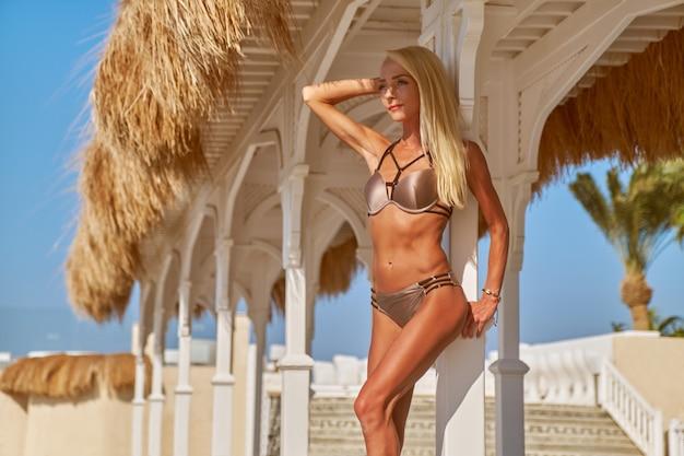 Femme sexy en bikini debout sur une chaise longue sous un auvent de paille à la piscine de la station