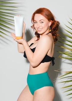 Femme sexy en bikini tenant un tube de crème solaire