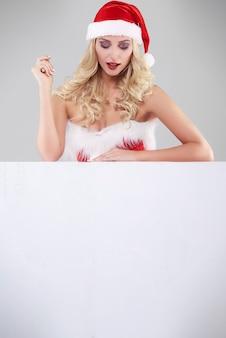 Femme sexy en costume de père noël sur mur gris