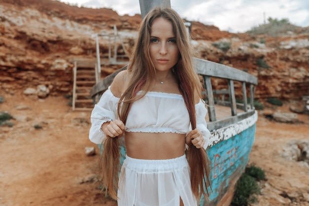 Femme sexy dans une robe blanche à un navire naufragé sur un bord de mer rocheux