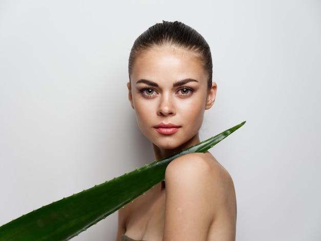 Femme sexy avec des épaules nues écarlates feuille verte
