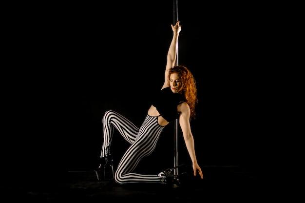 Femme sexy exerce la pole dance sur le fond sombre