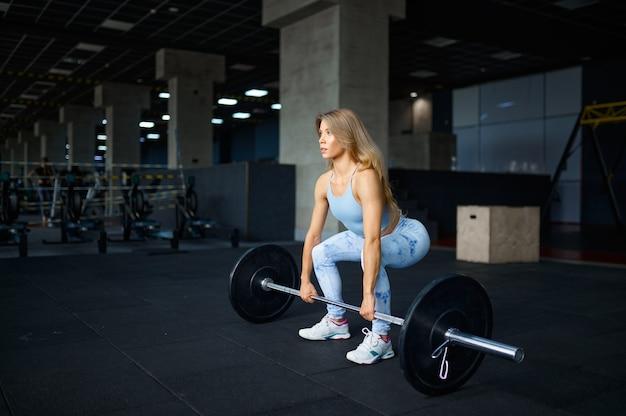 Femme sexy, faire de l'exercice avec haltères, entraînement physique en salle de gym