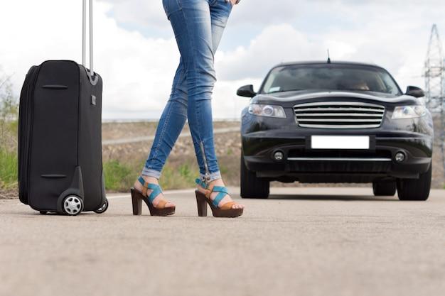Femme sexy faisant de l'auto-stop avec ses bagages