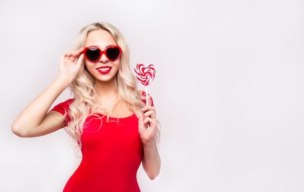 Femme sexy avec des lèvres rouges dans des coeurs de lunettes de soleil
