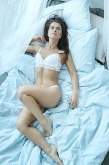 Femme sexy en lingerie allongée sur le lit