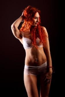 Femme sexy en lingerie en fond noir, cheveux roux