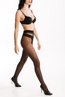 Femme sexy en lingerie noire élégante et bas