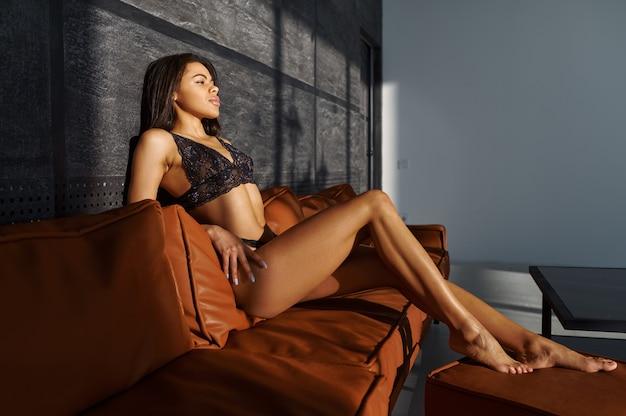 Femme Sexy En Lingerie Noire Posant Sur Un Canapé En Cuir Photo Premium