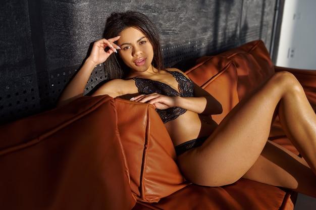 Femme sexy en lingerie noire posant sur un canapé en cuir